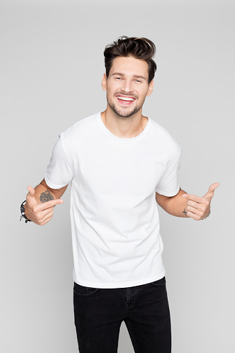 Cheerful young man pointing at himself 1048695348