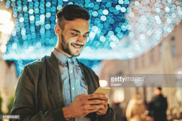 Cheerful young man reading nice text message from girlfriend in midnight