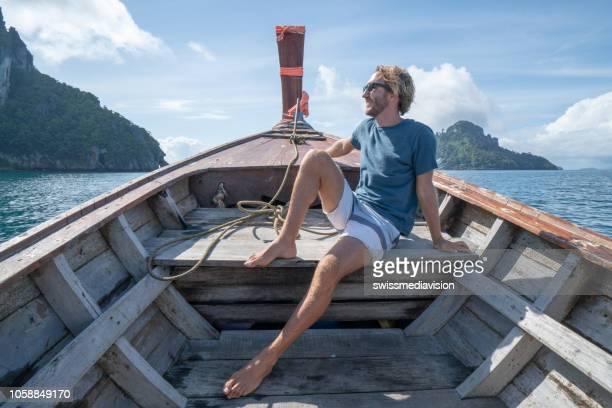 fröhlicher junger mann entspannend auf longtailboot in thailand. insel-hopper-konzept, urlaub. - asiatisches langboot stock-fotos und bilder