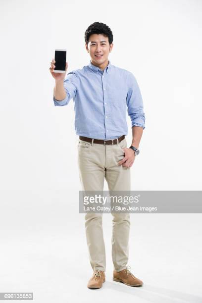 Cheerful young man showing a smart phone
