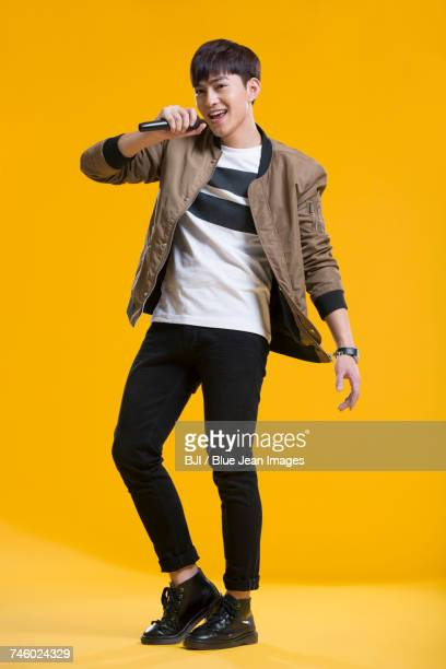 cheerful young man singing with microphone - cantor - fotografias e filmes do acervo