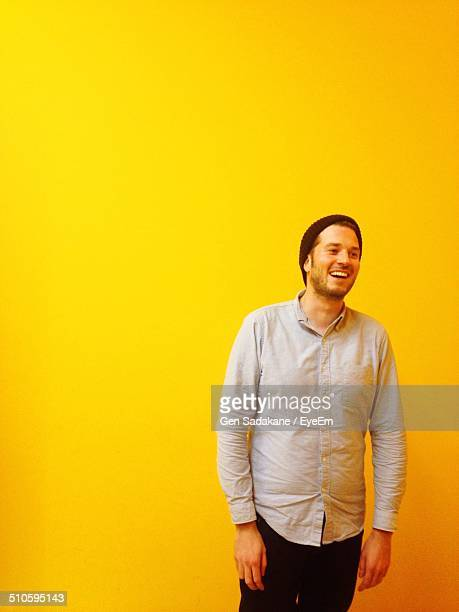 Cheerful young man standing against yellow background