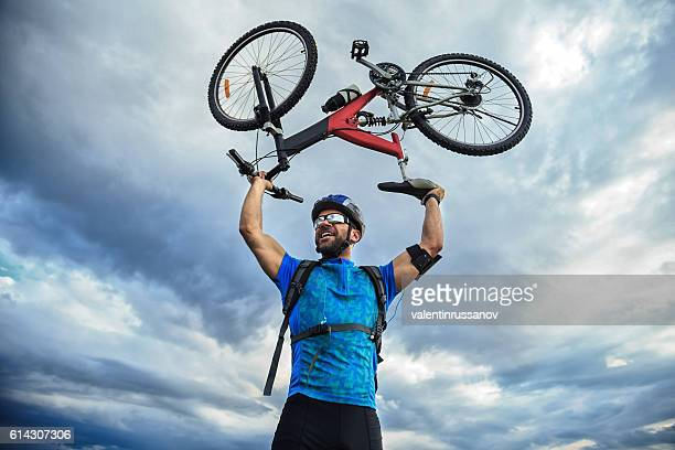 Cheerful young man standing on top and lifting his bike
