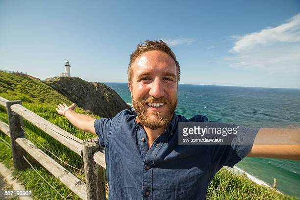 Cheerful young man takes a selfie portrait at Cape Byron