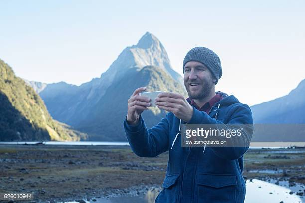 Cheerful young man takes selfie portrait using smart phone