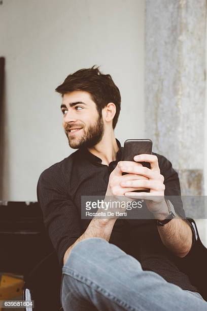 Cheerful young man texting friends with his smartphone