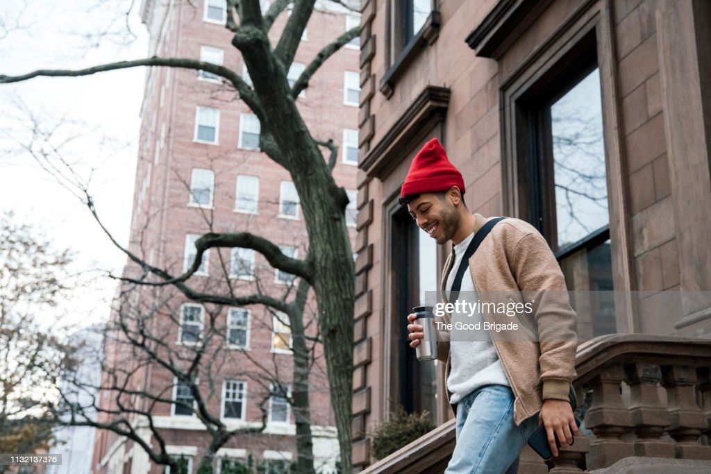 Cheerful young man walking down steps at brownstone : Photo