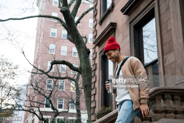 cheerful young man walking down steps at brownstone - leaving photos et images de collection