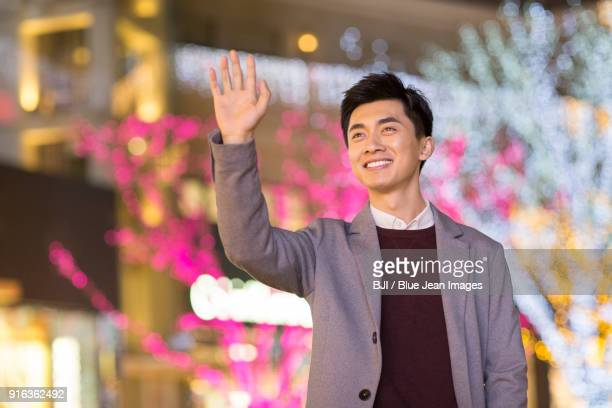 Cheerful young man waving