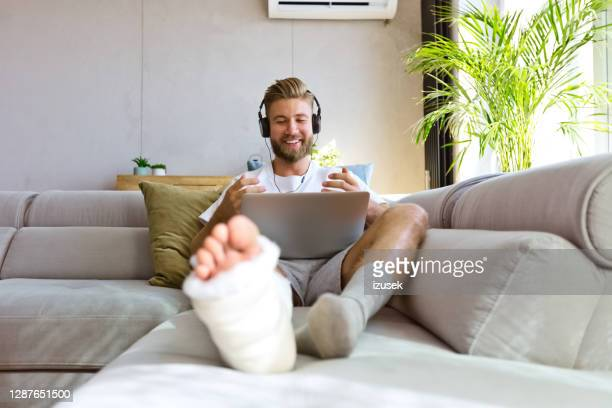 cheerful young man with broken leg during video call - recovery stock pictures, royalty-free photos & images