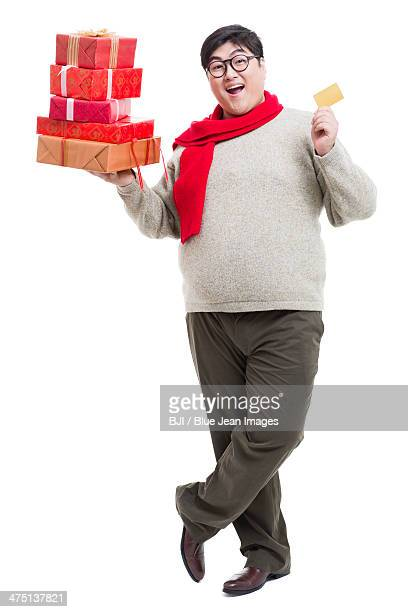 Cheerful young man with Chinese New Year's gifts and gold card