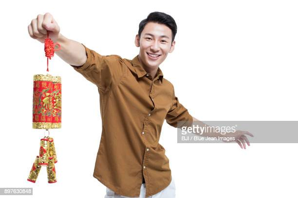 Cheerful young man with firecracker celebrating Chinese New Year