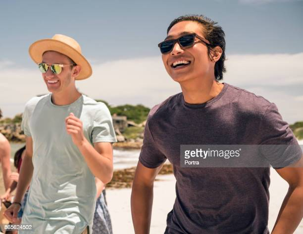 cheerful young man with friend at beach - only young men stock pictures, royalty-free photos & images