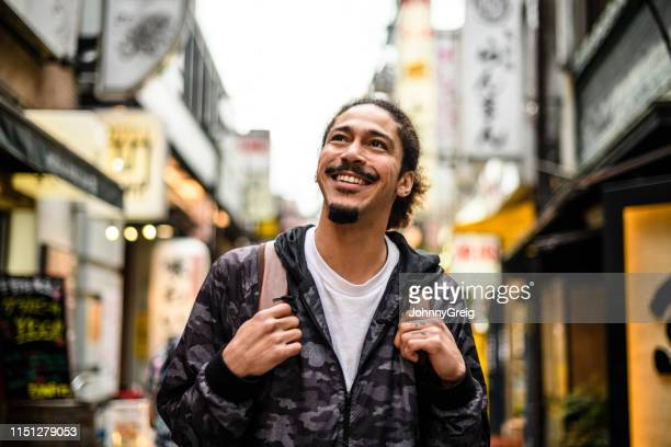 cheerful young man with goatee looking up in city street - goatee stock pictures, royalty-free photos & images
