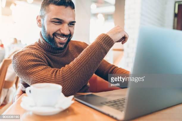 jovem alegre com laptop e expresso sentado no café - roupa quente - fotografias e filmes do acervo