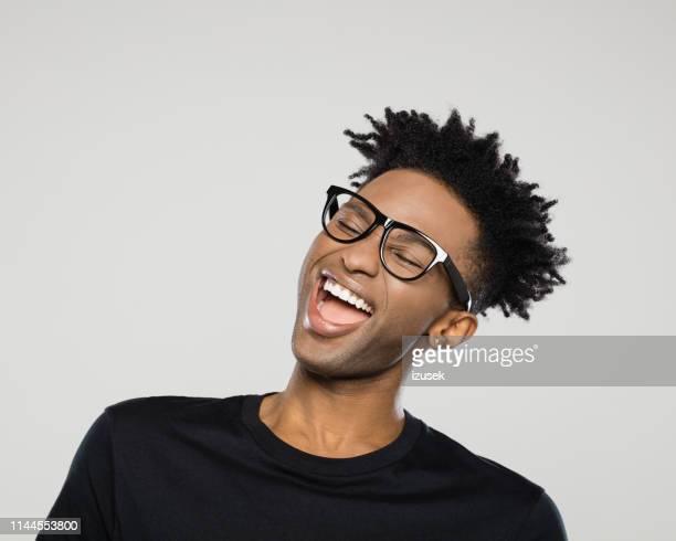 joven alegre con gafas de nerd - izusek fotografías e imágenes de stock
