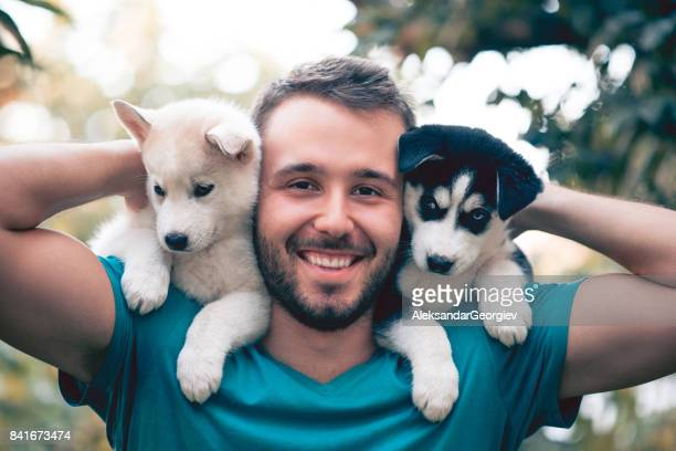 cheerful young men holding two lovely husky baby puppies - two animals stock pictures, royalty-free photos & images