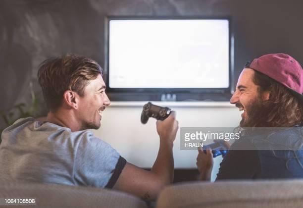 fröhliche junge männer spielen videospiel zu hause - computerspiel konsole stock-fotos und bilder