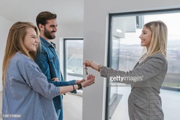 alegres novos proprietários de casas recebendo chaves de apartamento de um agente imobiliário - receber - fotografias e filmes do acervo