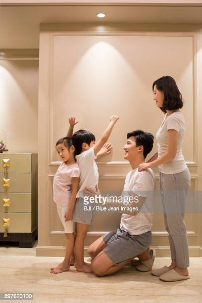 Cheerful young parents measuring their childrens height