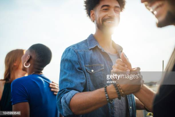 cheerful young people enjoying at party on rooftop - gesturing stock pictures, royalty-free photos & images