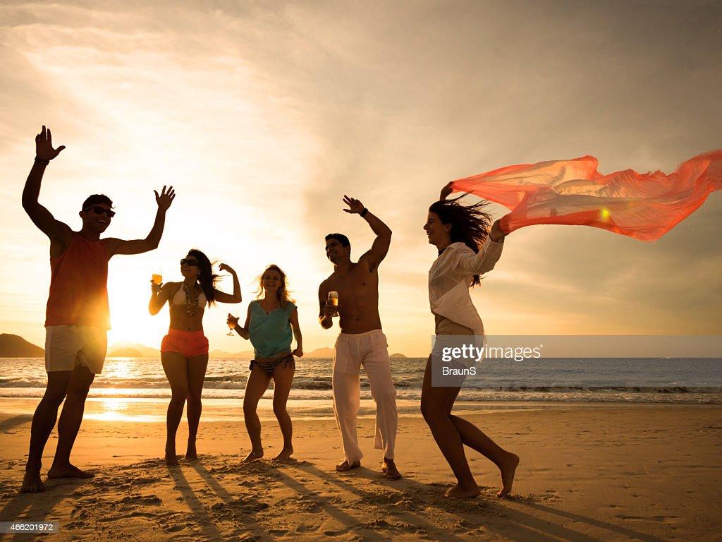 Fröhlich junger Menschen, beach party bei Sonnenuntergang. : Stock-Foto