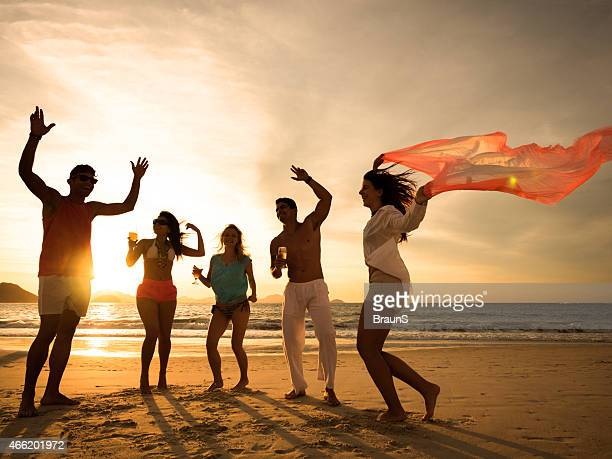 Cheerful young people having beach party at sunset.