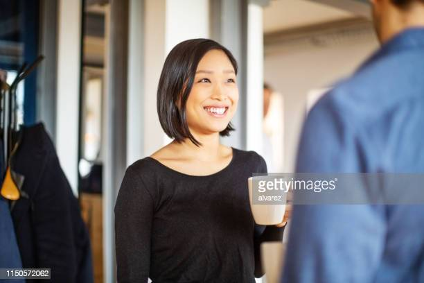 cheerful young people having coffee break in office - coffee break stock pictures, royalty-free photos & images