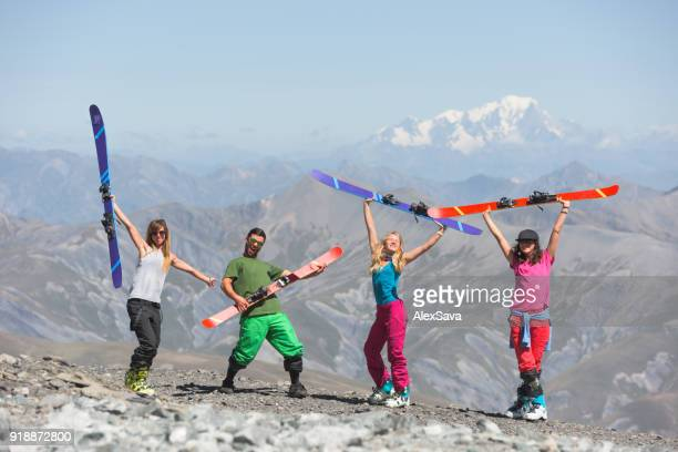 Cheerful young people holding up their skis