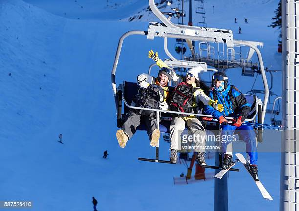 Cheerful young people making selfie on ski lift