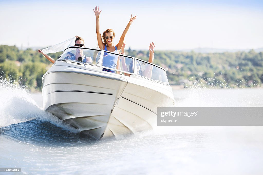 Cheerful young people riding in a speedboat : Stock Photo