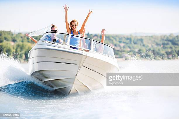 cheerful young people riding in a speedboat - watervaartuig stockfoto's en -beelden