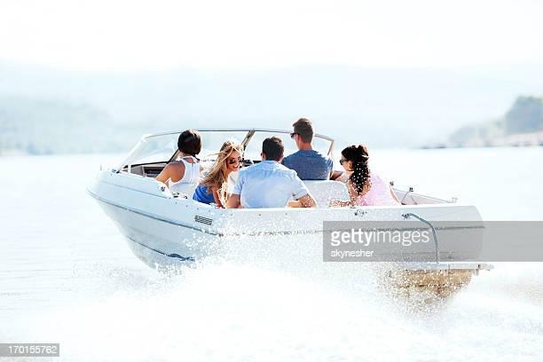 Fröhlich junger Menschen in einem speedboat fahren