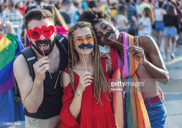 cheerful young people with paper mustaches at the pride festival - gender stereotypes stock pictures, royalty-free photos & images