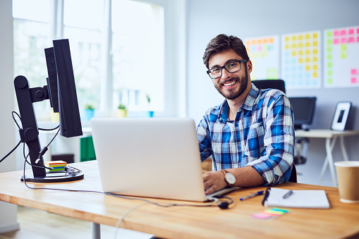 Cheerful young programmer looking at camera while working at his office 1151967132