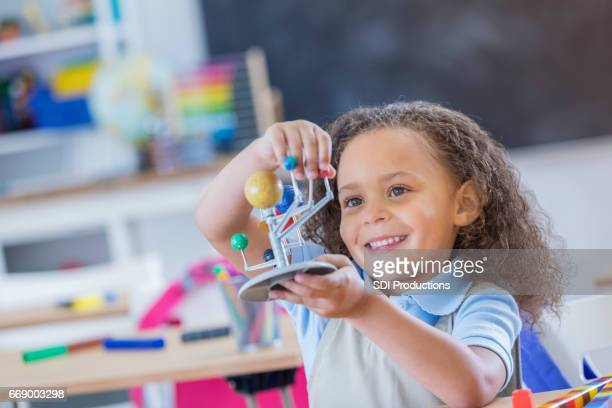 Cheerful young schoolgirl with solar system model