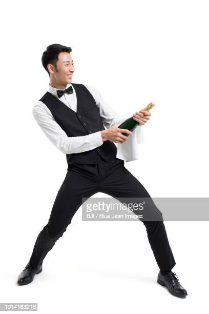 cheerful young waiter cheering with champagne bottle - legs spread open stock photos and pictures