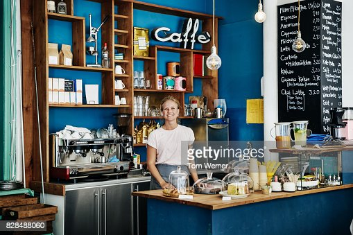 Cheerful Young Waitress Standing Proudly At Cafe Counter