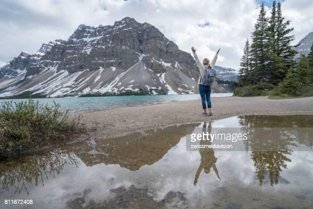 Fröhliche junge Frau Arme ausgestreckt am See