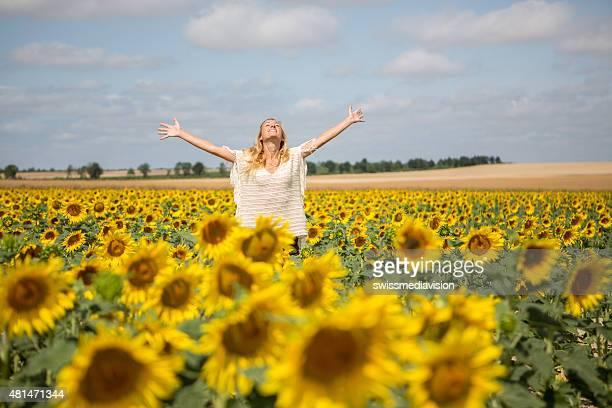 陽気な若い女性の腕を広げるひまわりのフィールドの真ん中