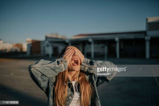 cheerful young woman covering her eyes outdoors - sinneswahrnehmung stock-fotos und bilder