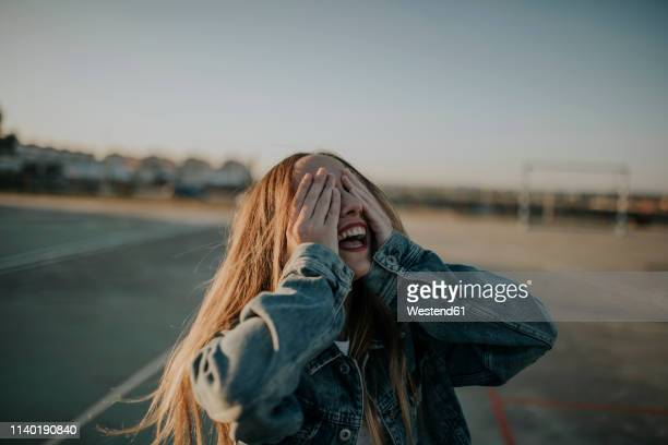 cheerful young woman covering her eyes outdoors - augen zuhalten stock-fotos und bilder