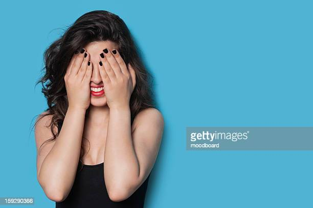 Cheerful young woman covering her face against blue background