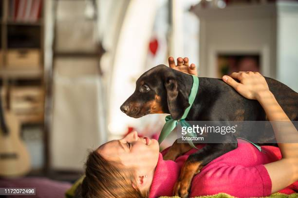 cheerful young woman cuddling her cute doberman puppy - dog knotted in woman stock pictures, royalty-free photos & images