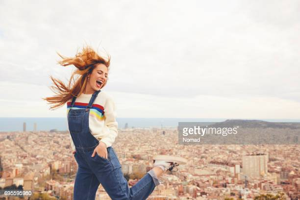 cheerful young woman dancing against cityscape - bib overalls stock pictures, royalty-free photos & images
