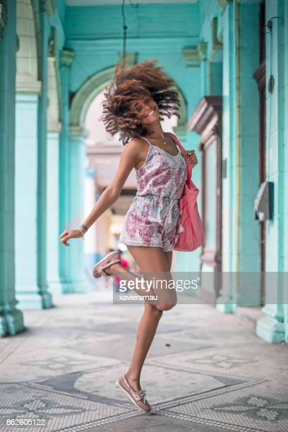 cheerful young woman dancing in corridor - havana stock pictures, royalty-free photos & images