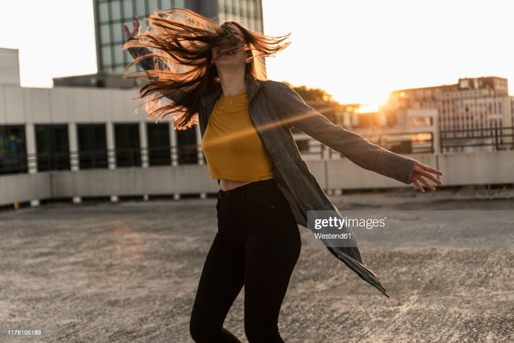 Cheerful young woman dancing on parking deck at sunset : Stock-Foto