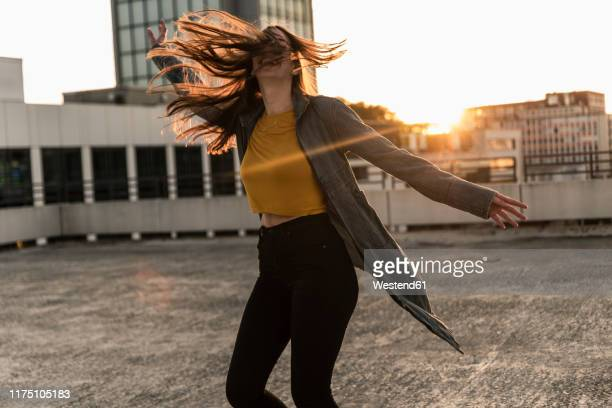 cheerful young woman dancing on parking deck at sunset - freedom stock-fotos und bilder