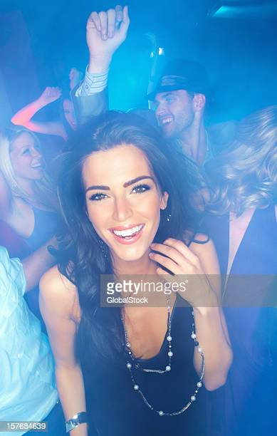 Cheerful young woman dancing with her friends at a disco