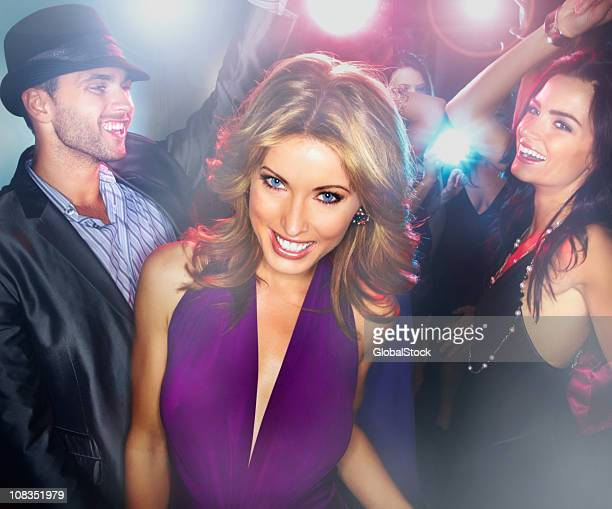 Cheerful young woman dancing with her friends in a nightclub